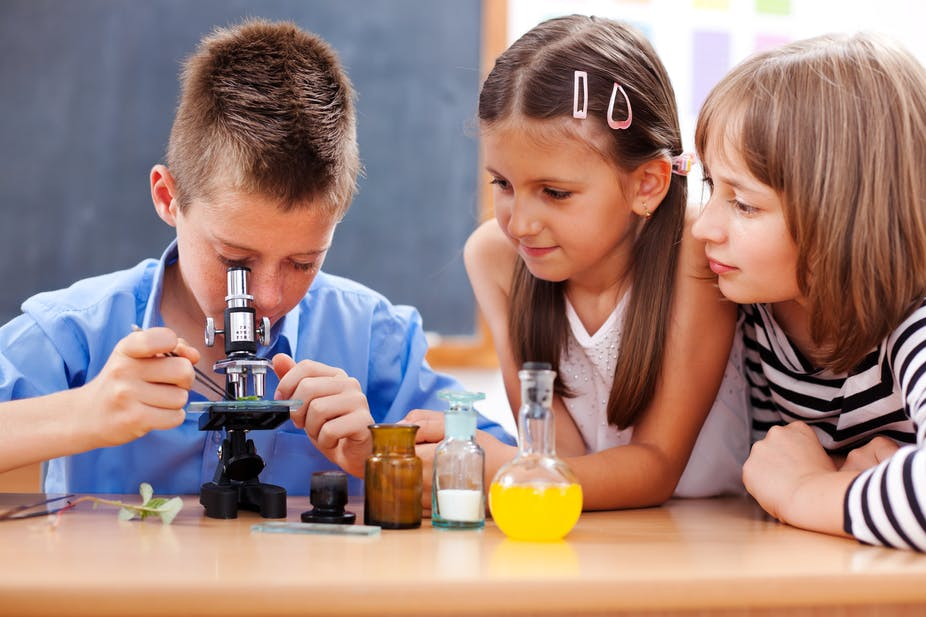 Young children take turns looking through the microscope.